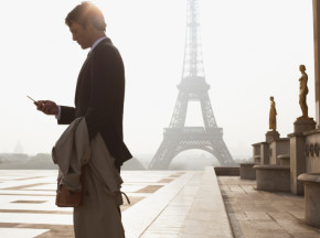Businessman outdoors with cellular phone by Eiffel Tower Frenc courses Estonia French Institute